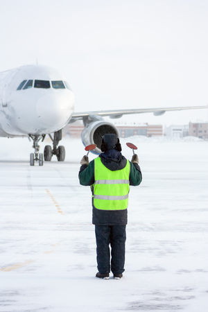 Airport marshaller meets the aircraft that parking in a cold winter weather Фото со стока - 95072831