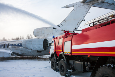 Airfield fire truck extinguishes aircraft after emergency landing in a cold winter weather Фото со стока - 95001725