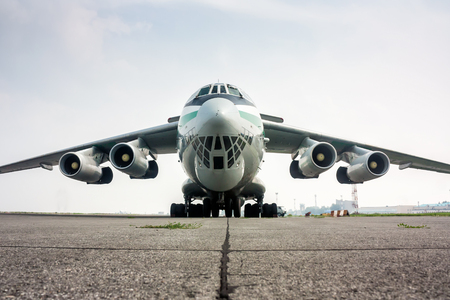 Close-up front view of big cargo airplane in a foggy airport