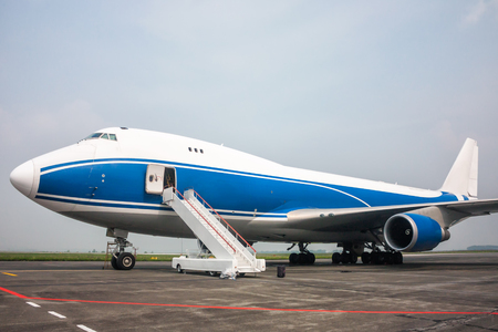 Cargo wide body airplane with opened door and boarding ramp