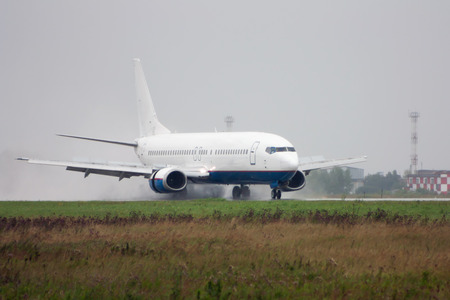 Passenger airplane heading on the runway with extended spoilers in heavy rain
