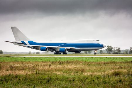 Big cargo airplane moves on the main taxiway in heavy rain Фото со стока