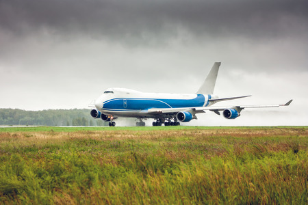Big cargo airplane moves on the runway in heavy rain