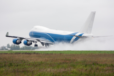 Wide body cargo airplane takes off in a heavy rain leaving behind a cloud of splatter Фото со стока
