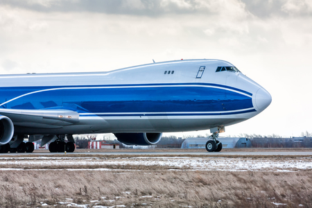 Close-up front view of big cargo aircraft on the runway at a cold winter airport Фото со стока