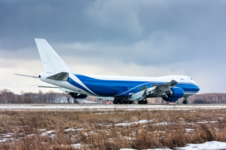 Big cargo plane moves on the runway at a cold winter airport