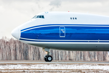 Close-up front view of big cargo airplane on the runway at a cold winter airport