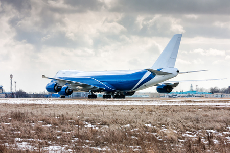Big cargo aircraft moves on the runway at a cold winter airport