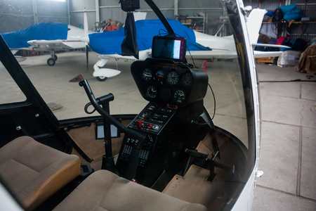 A view through the cabin of a small helicopter to the covered sports airplanes in the hangar Фото со стока