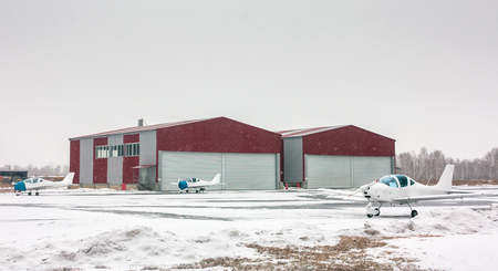Three small sports planes beside a hangars at the winter airfield
