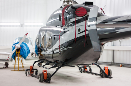 Helicopter and a small sports plane in the hangar