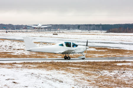 Small airplane moves on the taxiway and behind plane takes off at a cold winter airfield