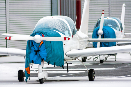 Two shrouded small sports airplanes beside to the hangars