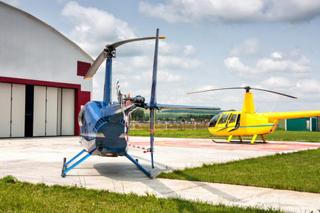 Helipad with two small helicopters beside the hangars