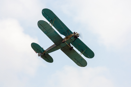 Retro airplane is flying Фото со стока