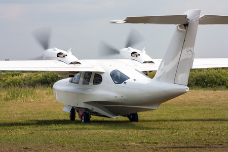 Amphibian airplane taxiing at the grass field Фото со стока