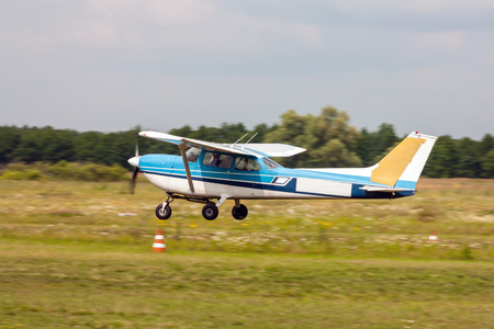 Small private airplane landing on the grass field