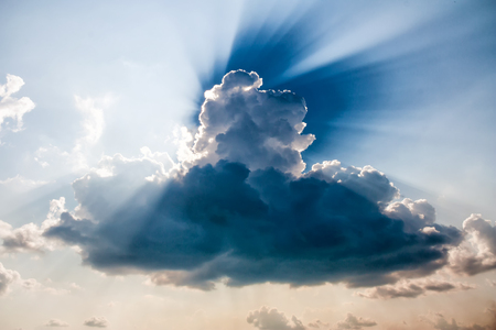 A muscular cloud with the rays of the sun peeping out from behind him Фото со стока