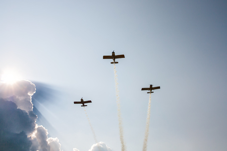 Three sports airplanes in flight releasing smoke against the background of a cumulus cloud because of which the sun shines