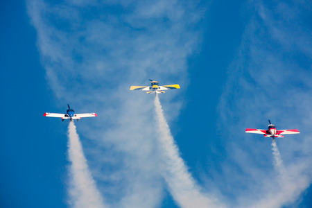 Acrobatic performance of three sports airplanes with the release of smoke Фото со стока