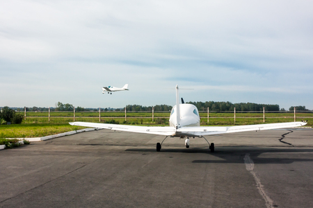 One small sports plane stands in the parking lot of the airfield and the other airplane comes in for landing