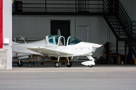 Small sports plane with opened cockpit canopy in the hangar