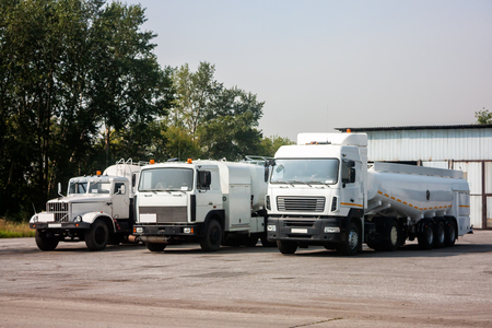 Three white tank truck aircraft refuelers in the parking lot near the garages Фото со стока
