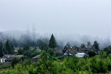 Fog in the mountain village Фото со стока