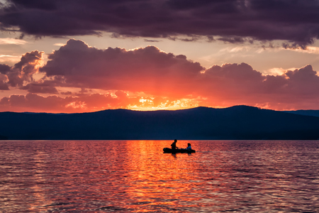 Romantic boat rides on the lake against the backdrop of the evening dawn