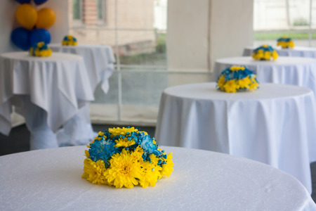 Tables with white tablecloths decorated with yellow-blue flowers