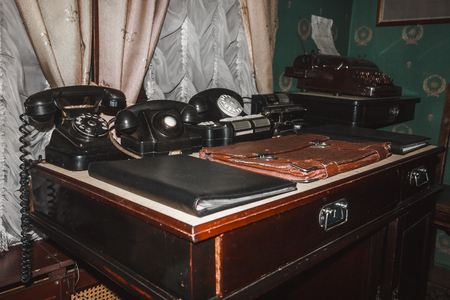 Retro phones, vintage cash register, old printing machine, folders and briefcase on the table Фото со стока