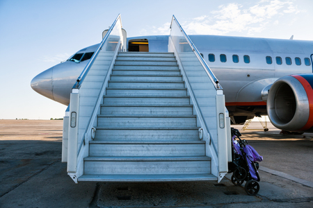 Airplane with a passenger boarding steps on the airport apron with a stroller prepared for the carriage of children Фото со стока