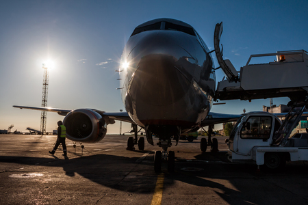 Front view of passenger aircraft ground handling at the airport apron in the morning sun Фото со стока