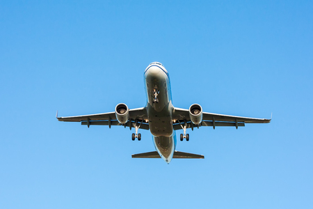 Passenger airplane in flight with landing gear released on blue sky background
