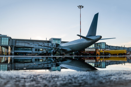 Ground handling of a passenger airplane parked to a jet bridge with reflection in a puddle