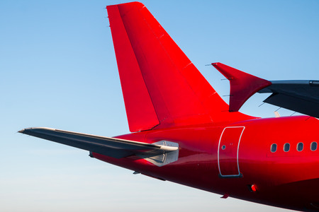 Tail and rear of the passenger airplane of red color against the blue sky