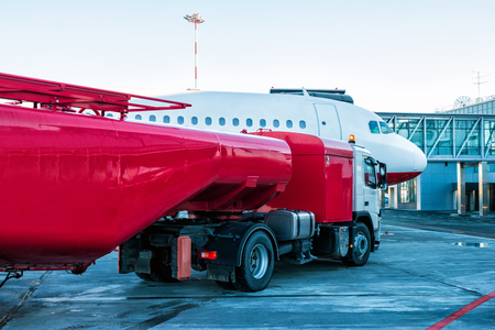 The red tanker refueling the aircraft parked to a boarding bridge at the airport apron