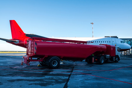 The red tanker refueling the plane parked to a boarding bridge at the airport apron