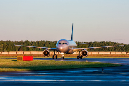 Taxiing passenger airplane at the early morning Фото со стока