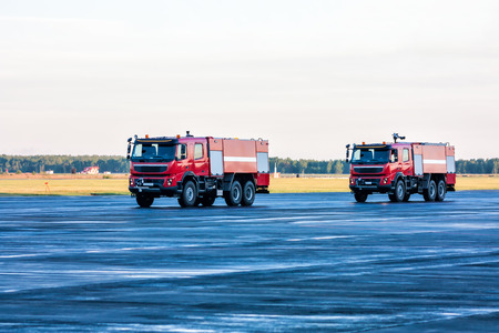 Two red airfield fire trucks at the airport apron