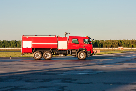 Red airfield fire engine at the airport apron Фото со стока