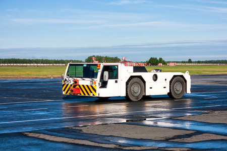 Airplane tow tractor at the airport apron
