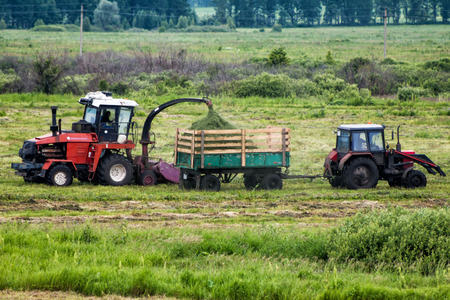 Combine harvester and tractor remove grass from the field Фото со стока - 99133987