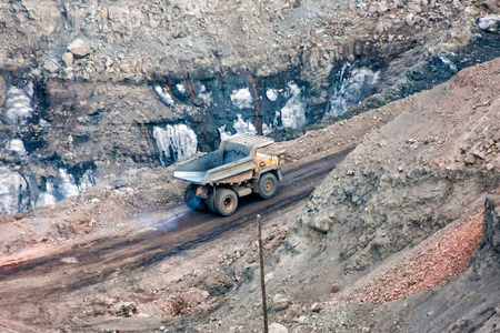 The quarry dump truck is moving in the mine Фото со стока - 99133990