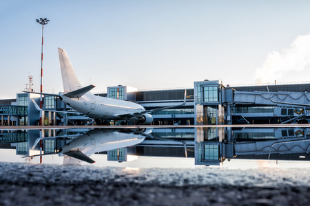 Passenger aircraft parked to a jetway with reflection in a puddle Фото со стока