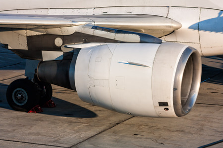 Close-up of engine and main landing gear of passenger aircraft Фото со стока