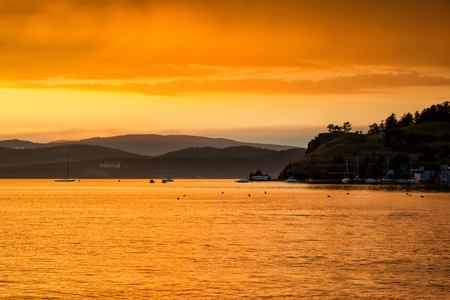 Scenic orange yellow sunset on the lake in a bay with yachts Фото со стока