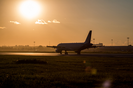 Passenger aircraft moves on the runway in the rays of the sunset