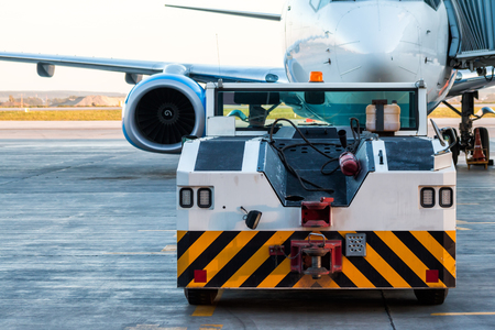The tow truck drive up at the passenger aircraft parked to a jet bridge Фото со стока