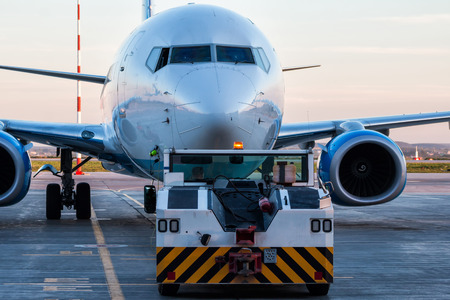 Tow tractor pushes the passenger aircraft at the airport apron